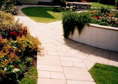 Slabbed garden trail with rendered plant bed
